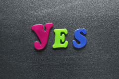 Word yes spelled out using colored fridge magnets. On metal surface royalty free stock photos