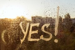 The word yes on the window with water drops on sunny background, yes written with white toothpaste.  stock images
