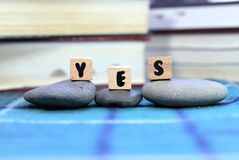 Word Yes. Concept of positive idea or positivity. Word Yes on wooden blocks. Selective focus on three letters YES on three wooden cubes placed on three pebble royalty free stock photos
