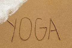 Word yoga in the sand. The word yoga written in the sand of a beach, with sea foam in a corner Stock Photography