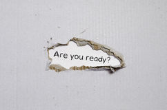 The word are you ready appearing behind torn paper. The word are you ready appearing behind torn paper Stock Photos