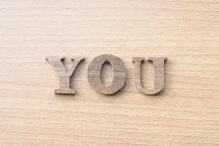 The word YOU from wooden alphabet. On wood background Royalty Free Stock Photography