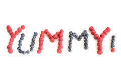 The word Yummy! written in raspberries and blueberries Royalty Free Stock Image