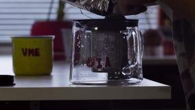 Worden de thee genezen bladeren gezet in de pot van de glasthee op lijst in keuken stock footage