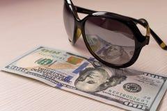 $ 100 worden weerspiegeld in de glazen op een beige achtergrond royalty-vrije stock fotografie