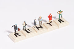 Wordgames- rente. Rente written of scrabble-stones with plastic figures around and on it Stock Photography