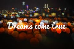 Wording Dreams come true with blurred background of night city and beautiful bokeh. Wording Dreams come true with blurred background of night city Royalty Free Stock Photo