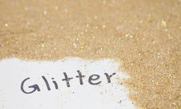 Wording Glitter on light gold glitter. On white background Stock Photography