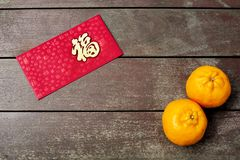 Wording of happiness on the red envelop with two tangerines. Wording of happiness embroidered on the red envelop with two tangerines, placed on a wooden table Royalty Free Stock Photography