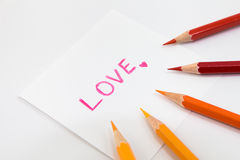 Wording  Love in pink color with little heart on the small paper , encircle with color pencils in warm tone Royalty Free Stock Image
