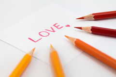 Wording  Love in Red color with little heart on the small paper , encircle with color pencils in warm tone Stock Photography