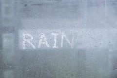 wording Rain, Water drop of rain on glass window with outdoor Stock Photos