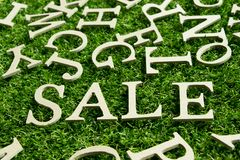 Wording sale on artificial green grass background. With english alphabet as decoration Royalty Free Stock Images