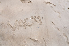 Wording Vacay on Beach Sand Background Stock Images