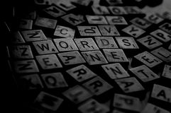 Words. A bunch of scrambled game board pieces with letters imprinted on them, focusing on Words with a shallow depth of field Stock Photos