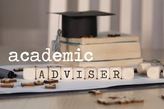 Words ACADEMIC ADVISER composed of wooden dices. Black graduate hat and books in the background. Closeup stock photos