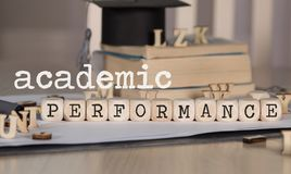 Words ACADEMIC PERFORMANCE composed of wooden dices. Black graduate hat and books in the background. Closeup stock images