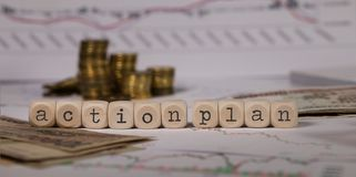 Words ACTION PLAN composed of wooden letter. Stacks of coins in the background. Closeup stock photo