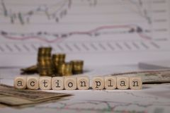 Words ACTION PLAN composed of wooden letter. Stacks of coins in the background. Closeup royalty free stock images