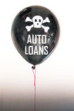 The words auto loans in white and a skull and cross bones on a balloon illustrating the concept of a debt bubble. Black balloon with the word `debt` representing stock photography