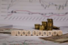 Words BAD LOANS composed of wooden letter. Stacks of coins in the background. Closeup royalty free stock image