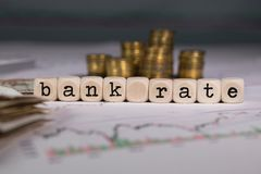 Words BANK RATE composed of wooden letter. Stacks of coins in the background. Closeup royalty free stock images