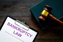 Words bankruptcy law written on the documents near judge gavel on dark wooden background top view copy space stock image