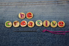 The words be creative spelled with lettered buttons. 'be creative' words spelled out in lettered buttons on a denim background Stock Images