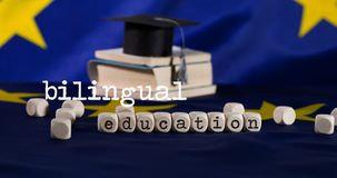 Words BILINGUAL EDUCATION  composed of wooden letters. Black graduate hat on EU flag in the background. Closeup stock image