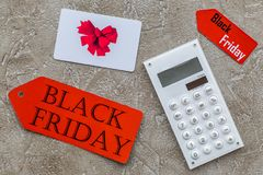 Words black friday on red label near card and calculator on light background top view Stock Image