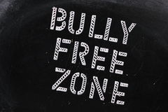 Bully Free Zone. The words Bully Free Zone in chalk stencil letters on a well used blackboard royalty free stock photography