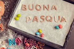 Words Buona Pasqua as Happy Easter in italian language. Made of raw dough letters. Easter baking concept: raw dough for biscuit, colorful eggs, cutters in the Stock Photo
