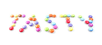 Words in candy. The word 'tasty' written with sugar-coated candy on a white surface Stock Image