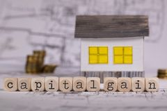 Words CAPITAL GAIN composed of wooden letter. Small paper house in the background. Closeup stock photography