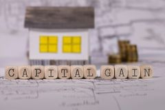 Words CAPITAL GAIN composed of wooden letter. Small paper house in the background. Closeup royalty free stock photo