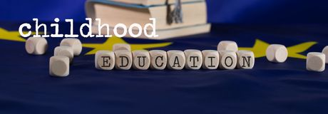 Words CHILDHOOD  EDUCATION composed of wooden letters. Black graduate hat on EU flag in the background. Closeup royalty free stock photo