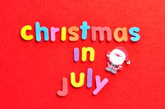 The words christmas in July on a red background and a Santa Clause figurine. The words christmas in July in colorful letters on a red background and a Santa Royalty Free Stock Image