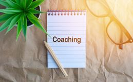 Words COACHING on wooden paper background. Business and education concept stock images
