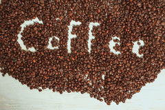 The words coffee written against scattered natural coffee Stock Photos