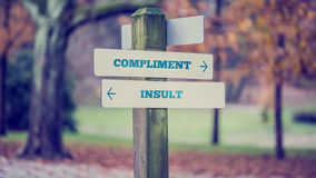 Words Compliment and Insult in a conceptual image. Retro vintage style image of a rural signboard with two signs saying - Compliment - Insult - pointing in stock photography