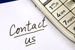 The words Contact us with a cellular phone. Isolated on blue Stock Images