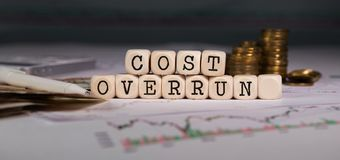 Words COST OVERRUN composed of wooden letter. Stacks of coins in the background. Closeup royalty free stock photography