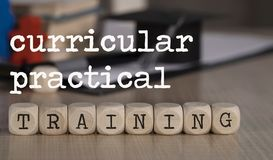 Words CURRICULAR PRACTICAL TRAINING composed of wooden dices. Black graduate hat and books in the background. Closeup stock images