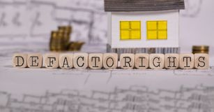 Words DE FACTO RIGHTS composed of wooden letter. Small paper house in the background. Closeup stock photography