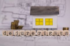 Words DE JURE RIGHTS composed of wooden letter. Small paper house in the background. Closeup royalty free stock images