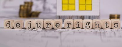 Words DE JURE RIGHTS composed of wooden letter. Small paper house in the background. Closeup royalty free stock image