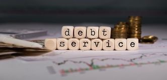 Words DEBT SERVICE composed of wooden letter. Stacks of coins in the background. Closeup stock photos