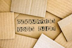 Words Declutter Your Life make by black alphabet stamps on cardb. Oard with some piece of cardboard stock image