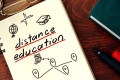 Words distance education written in the notepad. Royalty Free Stock Photography