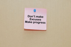 Words of Don't Make Excuses Make Progress on sticky color papers stick on brown cardboard. Background Stock Photography